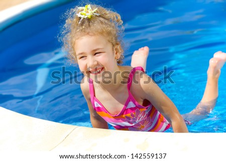 Pretty little girl in swimming pool outdoors