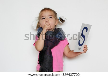 Pretty little girl in the scarf with S letter in one hand giving a cough in the fist because of cold, indoor isolated portrait over the white background - stock photo