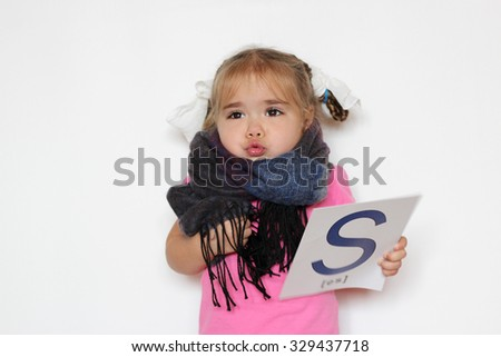 Pretty little girl in the scarf with S letter in one hand huddling up from cold, indoor isolated portrait over the white background - stock photo