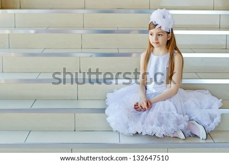 Pretty little girl in white dress sitting on the steps
