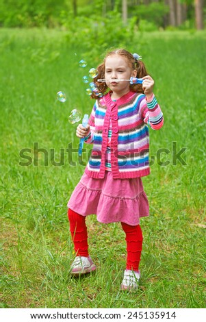 Pretty little girl inflates soap bubbles. Happy childhood - stock photo