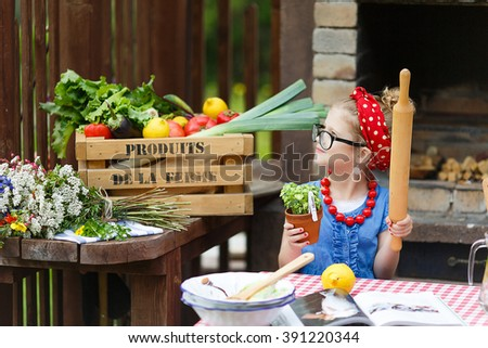 Pretty little girl is cooking the dinner - stock photo