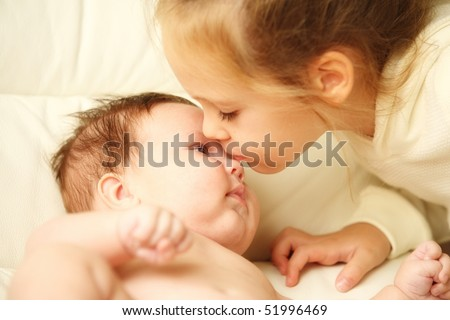 pretty little girl kissing her adorable baby brother - stock photo