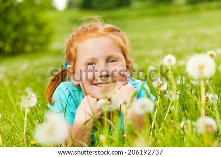 Pretty little girl lays on a grass