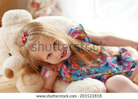 Pretty little girl lies on big soft toy bear and looks at camera in studio