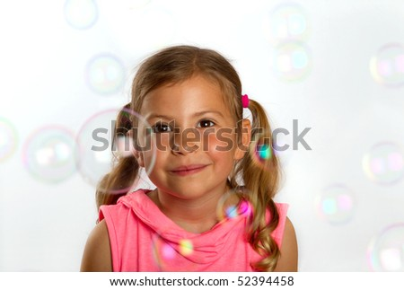 Pretty little girl looking at large bubbles