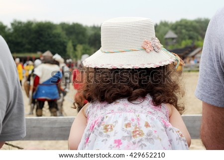 Pretty little girl looking on the medieval knights performance during historical festival, theatrical performances involving the troubadours, knights. - stock photo