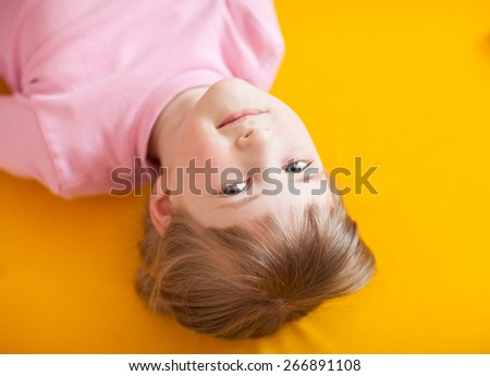 Pretty little girl lying head over heels on the yellow mat - stock photo