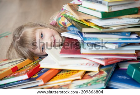Pretty little girl lying on the floor among books - stock photo