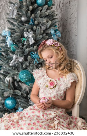 pretty little girl near the new year tree. beautiful girl in a wreath and dress near Christmas tree waiting for holiday