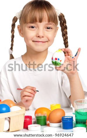 Pretty little girl painting Easter eggs isolated on white background - focus on egg