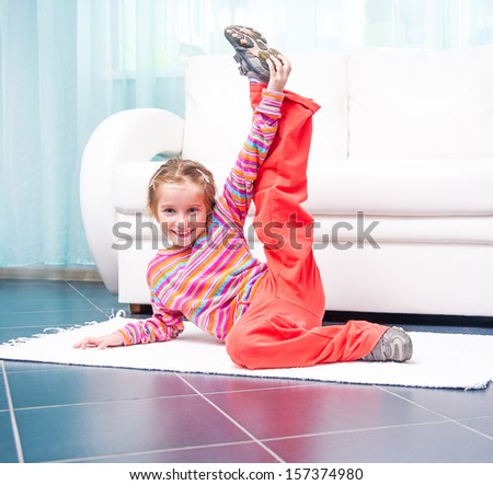 pretty little girl playing sports at home in front of a white sofa