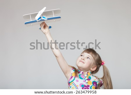 Pretty little girl playing with a toy plane, neutral background - stock photo