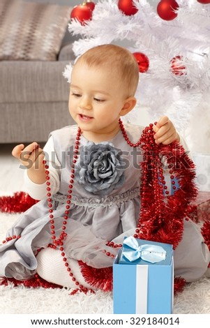 Pretty little girl playing with christmas ornaments under christmas tree. - stock photo