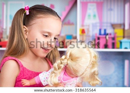 Pretty little girl playing with doll - stock photo