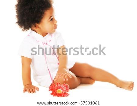 Pretty little girl reaching for flower on white background - stock photo
