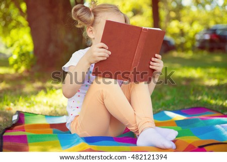 Pretty little girl reading red book in green summer park