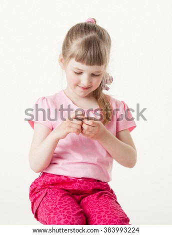 Pretty little girl reading the text on a card, white background