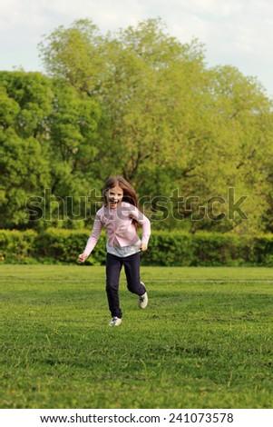 Pretty little girl runs across the field on a decline - stock photo