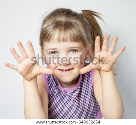Pretty little girl showing her palms, neutral background - stock photo