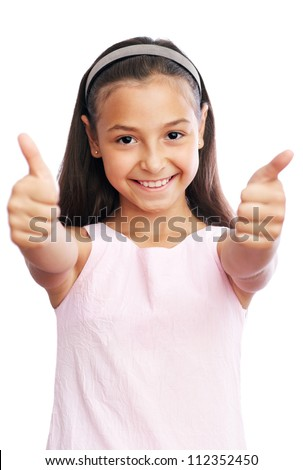 Pretty little girl showing thumbs up against white background - stock photo