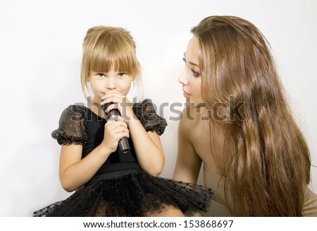 Pretty little girl singing in microphone, mother and little girl with a microphone