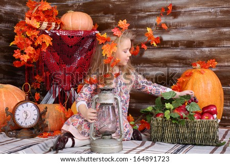 Pretty little girl sits on floor and takes out grape from basket with fruits in room with pumpkins and autumn interior.