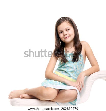 pretty little girl sitting and smiling isolated on the white - stock photo