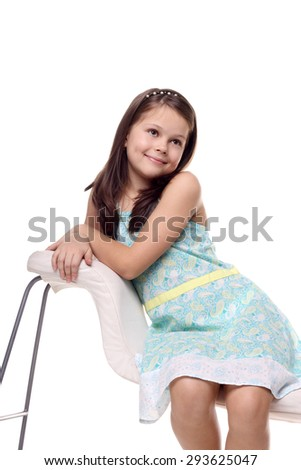 pretty little girl sitting and smiling isolated on the white