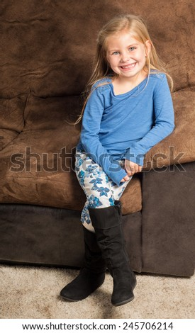 Pretty little girl sitting on a brown sofa with a big smile wearing black boots - stock photo