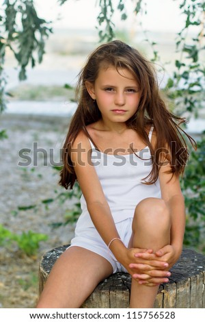 Pretty little girl sitting on a tree stump - stock photo