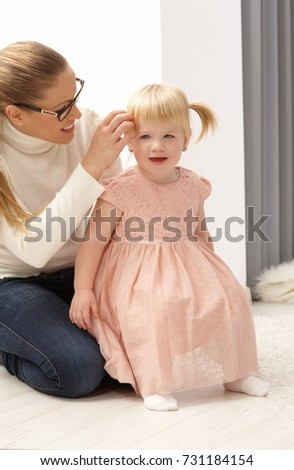 "Pretty little girl sitting on mothers"" lap, preparing for celebration."