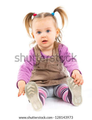 Pretty little girl sitting on white background in studio. Vertical view
