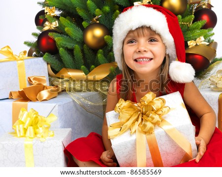 Pretty little girl smiling with present near the Christmas tree - stock photo