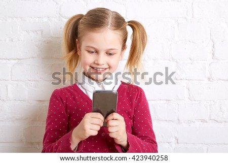 Pretty little girl standing on a light background, holding a phone and writing message. - stock photo
