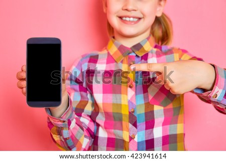 Pretty little girl standing on a pink background holding a phone and showing a finger on the screen. Close up. Copy space. - stock photo