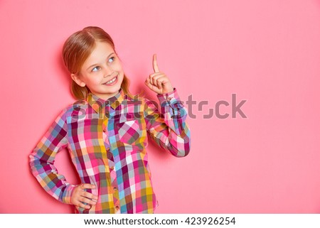 Pretty little girl standing on pink background with raised finger up. Copy space.