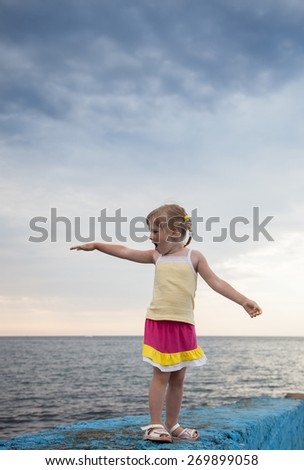 Pretty little girl standing on the embankment on sea background - stock photo