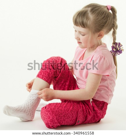 Pretty little girl trying on sock, white background - stock photo