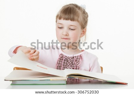 Pretty little girl turning over pages of a book, white background