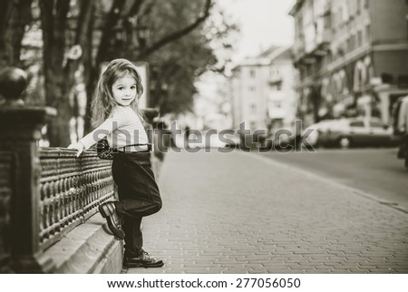 Pretty little girl walking on the city street - stock photo