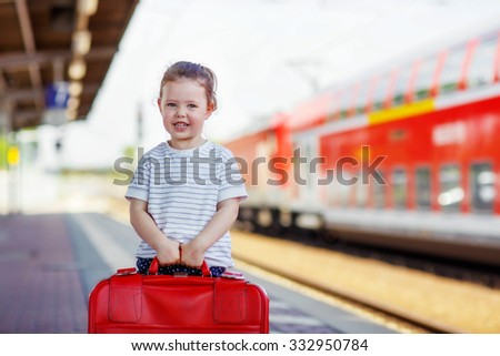 Pretty little girl walking with big red suitcase on a railway station. Kid waiting for train and happy about a journey. People, travel, lifestyle concept - stock photo