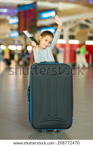 pretty little girl waving goodbye at airport - stock photo
