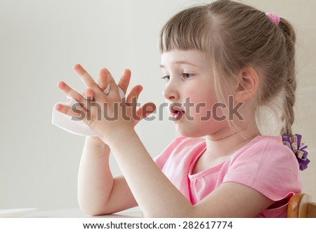 Pretty little girl wiping her hands with a vissue at home