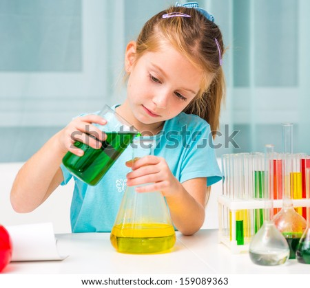 pretty little girl with flasks for chemistry