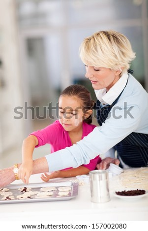 pretty little girl with grandmother baking cookies together at home - stock photo