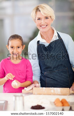 pretty little girl with her granny baking cookies at home - stock photo