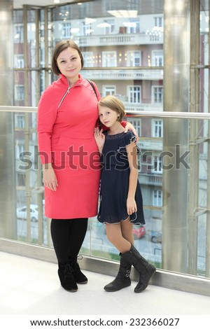 pretty little girl with her mother posing in the hall