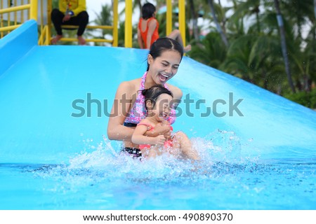 Pretty little girl with her mother sliding in swimming pool outdoors