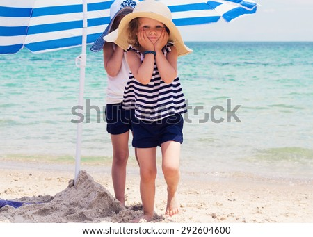 Pretty little girls (sisters) on the beach. Selective focus. - stock photo